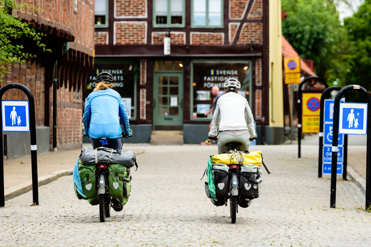 Ystad, Sweden - August 1, 2016: Real people in everyday life. Two traveling tourists on bikes seen from behind with full packs on their racks.