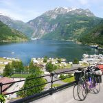 Geiranger, Norway - July 3, 2008: A fully packed bike of a travelling person is leaning against a fence in front of the fantastic scenery of Geiranger fjord in Western Norway in summer. Below the street you can see the small village of Geiranger with its camping sites.